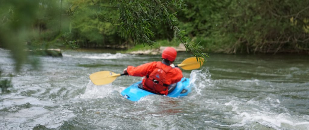 Kajakfahrer fährt sicher Boot nach Sicherheitsschulung.