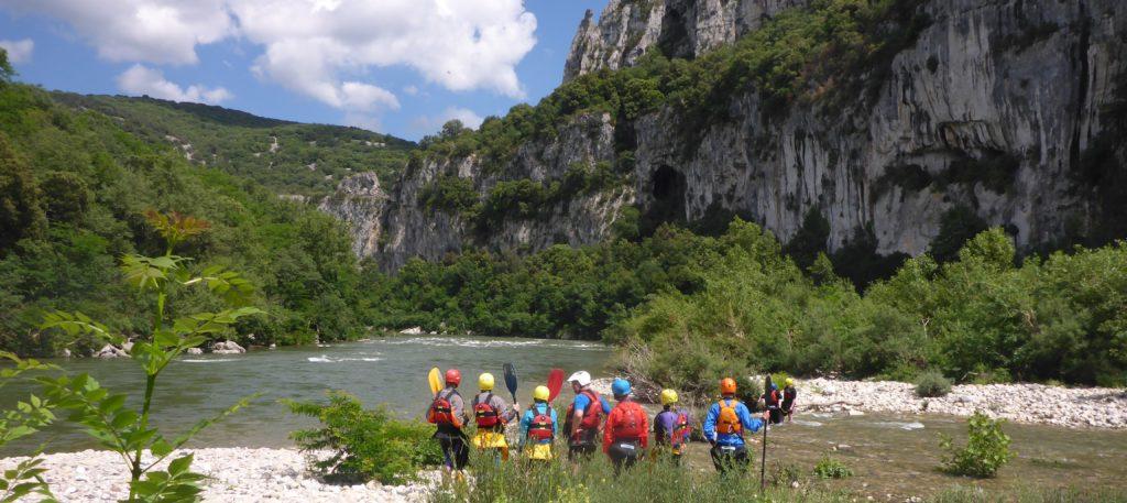 Kajakgruppe beim scouten auf Kiesbank der Ardéche kurz vor der Pont d'Arc in Südfrankreich.