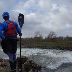 Kajakfahrer am Ufer besprechen und scouten Hochwasser.